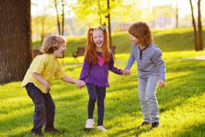 Three childrern holding hands smiling while standing in a park